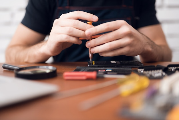 Mani di riparazione smartphone con cacciavite per computer.
