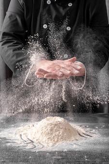 Mani di sfregamento del cuoco unico con farina