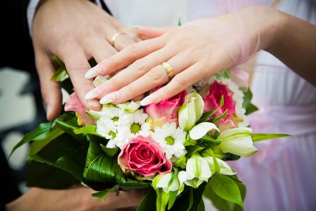 Mani di sposi con bouquet da sposa