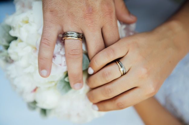 Mani di sposi con fedi nuziali