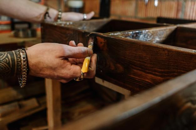 Mani di un carpentiere che spazzola una mobilia di legno all'officina del mestiere