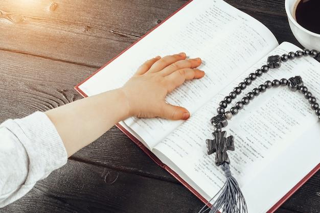 Mani di un giovane bambino cristiano e della sacra bibbia sulla tavola di legno