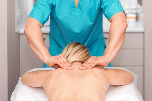 Mani di un massaggiatore che fa massaggio alla schiena di una donna. giovane donna che ha procedura di scultura del corpo. regolazione posteriore della chiropratica. osteopatia, medicina alternativa, concetto di sollievo dal dolore.