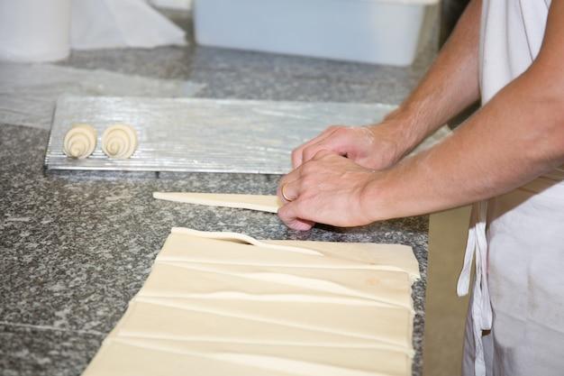Mani di un panettiere che produce i croissant su fondo grigio