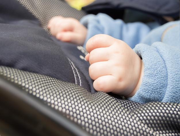 Mani di un pugno del bambino, messa a fuoco selettiva, il bambino è nel passeggino