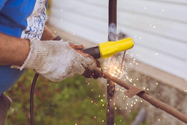 Mani di un saldatore vicino con fuoco e scintille