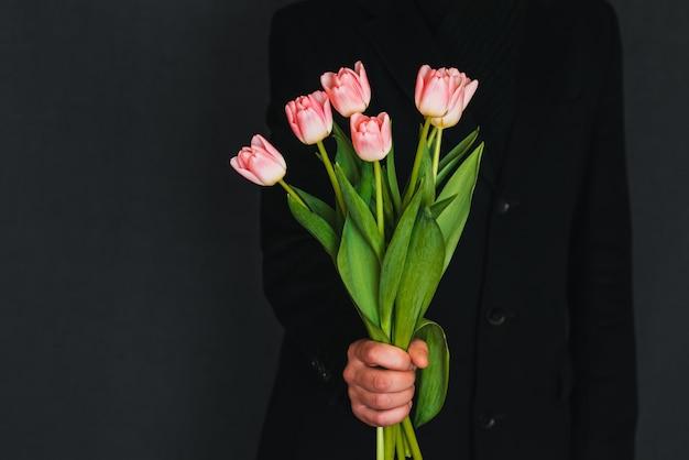 Mani di un uomo che dà un mazzo di tulipani rosa