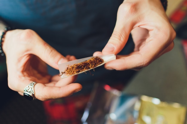 Mani di un uomo che rotola una sigaretta. il concetto di marijuana, droghe, dipendenza.