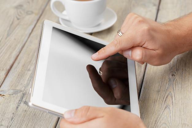 Mani di un uomo che tiene il dispositivo in bianco della compressa sopra una tavola di legno dell'area di lavoro