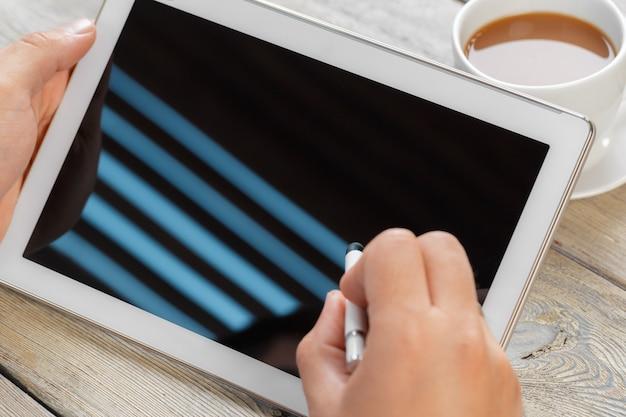 Mani di un uomo che tiene il dispositivo tablet bianco su un tavolo di lavoro in legno