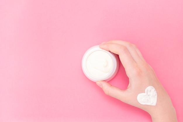 Mani di una bella donna ben curata con un barattolo di crema sul rosa