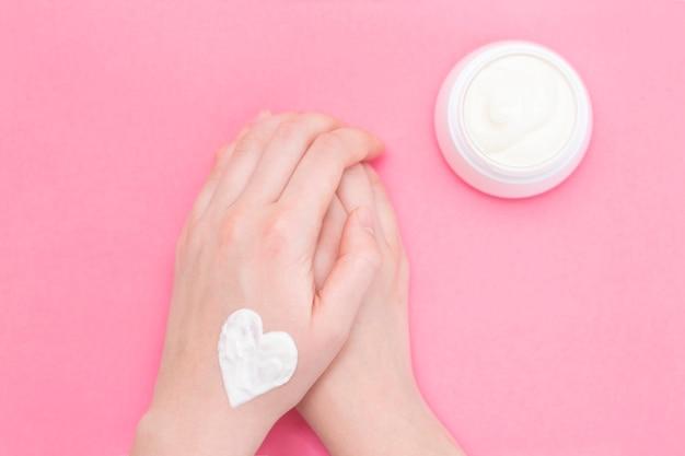 Mani di una bella donna ben curata con un vasetto di crema su uno sfondo rosa strutturale