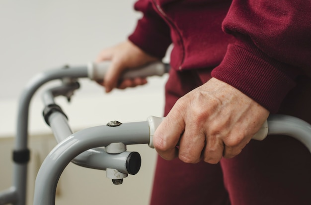 Mani di una donna anziana sulle maniglie di un camminatore. riabilitazione e concetto di assistenza sanitaria.