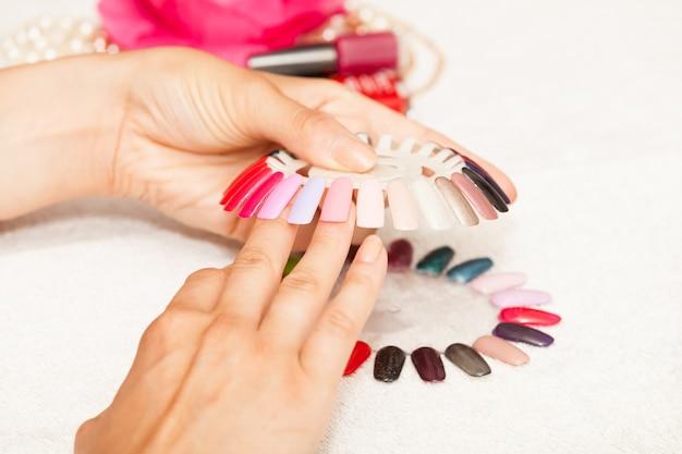 Mani di una donna che sceglie il colore del suo smalto per unghie