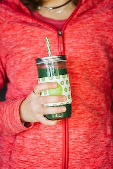 Mani di una donna che tiene un barattolo di succo di spremitura a freddo verde detox