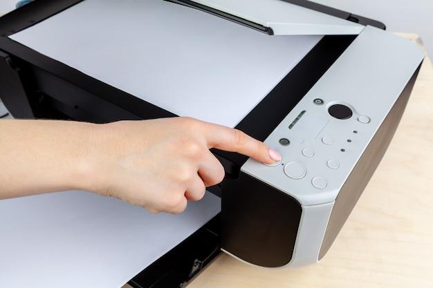 Mani di una donna che usando una fine della fotocopiatrice su
