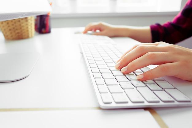 Mani di una donna dell'ufficio digitando