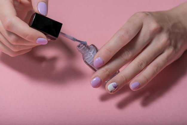 Mani di una donna su uno sfondo rosa con manicure viola e una bottiglia aperta di chiodo