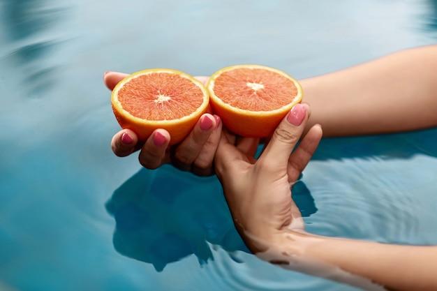 Mani di una giovane donna che tiene un pompelmo rosso vicino con acqua blu. cibo salutare