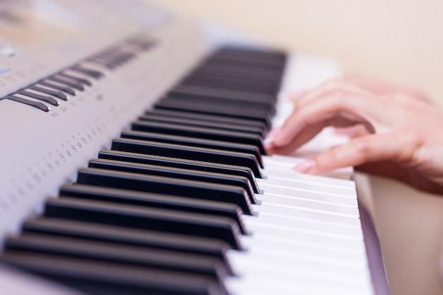 Mani di una giovane ragazza accanto ai tasti del pianoforte. la ragazza suona il piano. esecuzione di un brano musicale su un pianoforte