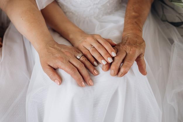 Mani di una giovane sposa e mani dei genitori, diversa generazione, giorno delle nozze