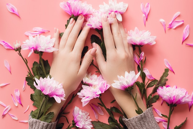 Mani di una ragazza con una manicure delicata in fiori