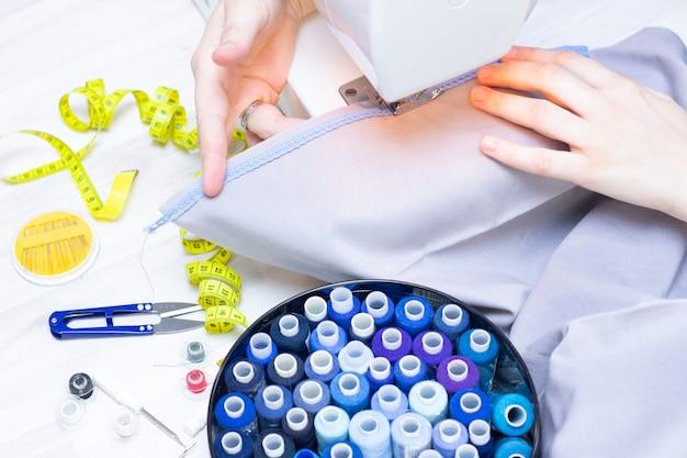 Mani di una sarta su una macchina da cucire.