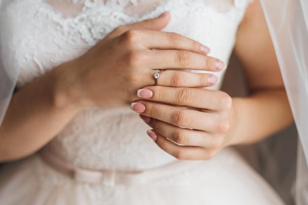 Mani di una sposa con tenera manicure francese e prezioso anello di fidanzamento con diamante lucido, abito da sposa