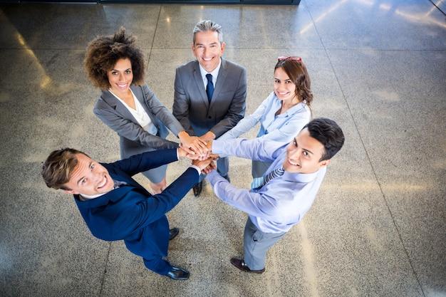 Mani di uomini d'affari accatastati gli uni sugli altri in ufficio