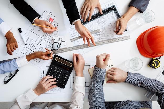 Mani di uomini d'affari sul tavolo bianco con documenti e bozze