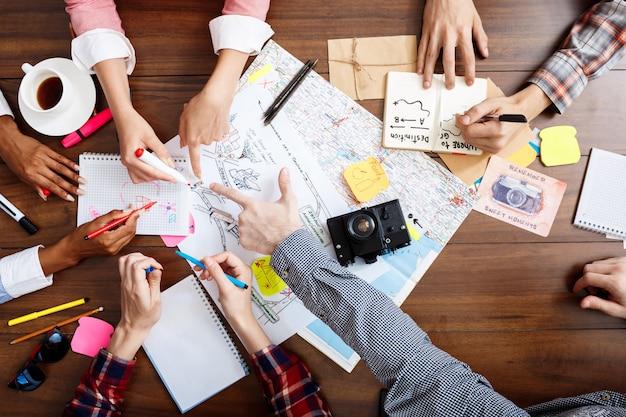 Mani di uomini d'affari sul tavolo di legno con documenti e bozze