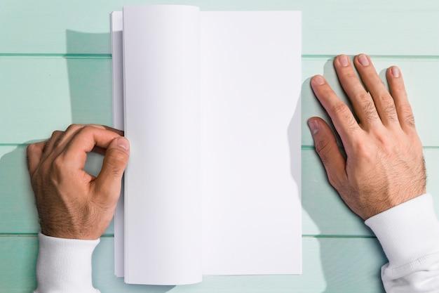 Mani di vista superiore che girano le pagine vuote bianche