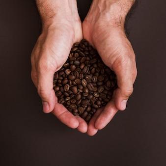 Mani di vista superiore che tengono i chicchi di caffè