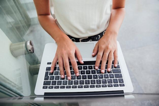 Mani di vista superiore sulla tastiera del computer portatile