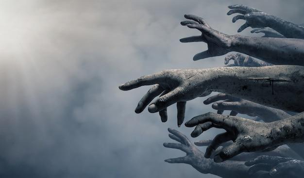 Mani di zombie che si alzano nella notte oscura di halloween.