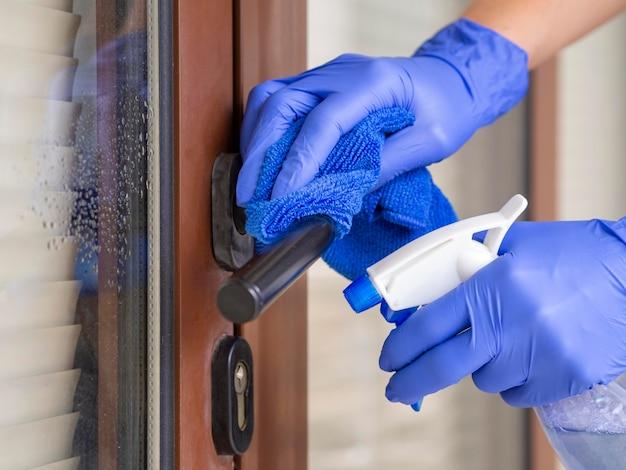 Mani disinfettano la maniglia della porta con abluzione e panno
