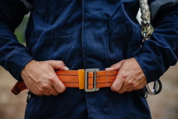 Mani e cintura di un operaio falegname in primo piano in abiti da lavoro e con una cintura. energia.