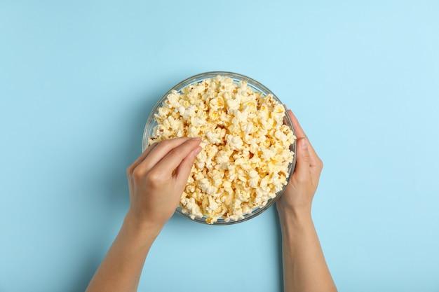 Mani e ciotola maschii con popcorn su spazio blu