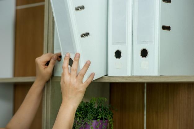 Mani e file di giovani impiegati trova qualcosa sugli scaffali. e il suo spazio di lavoro. il suo file bianco