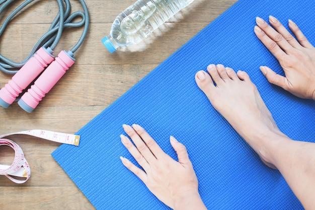 Mani e posizione del piede yoga con attrezzature sportive, stile di vita sano e lavoro a casa