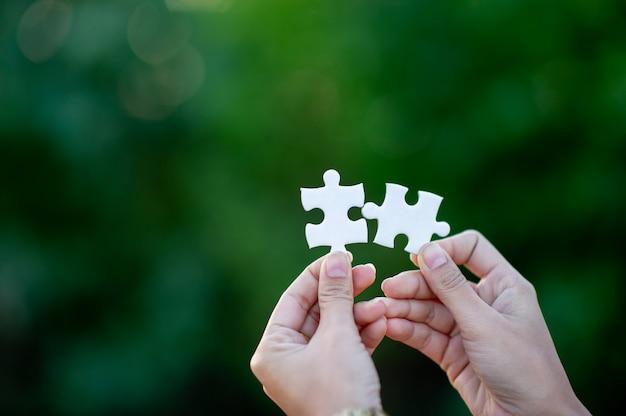 Mani e puzzle bianchi immagine di close-up e integrazione concetto di business e unità