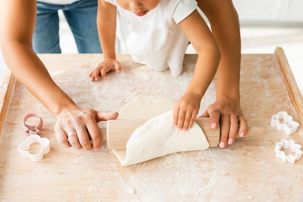 Mani facendo uso del rullo della cucina sulla pasta dei biscotti