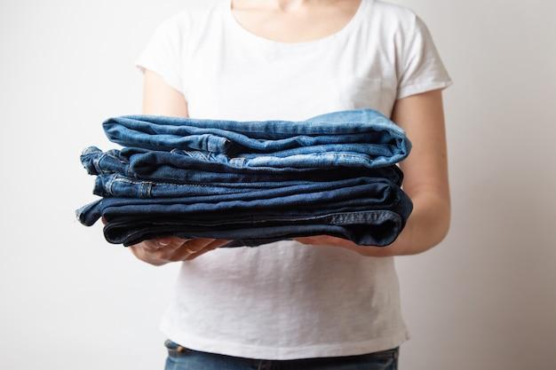 Mani femminili caucasiche del primo piano che tengono tre paia dei jeans blu del denim.