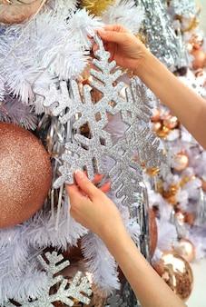 Mani femminili che appendono un ornamento del fiocco di neve di scintillio sull'albero di natale