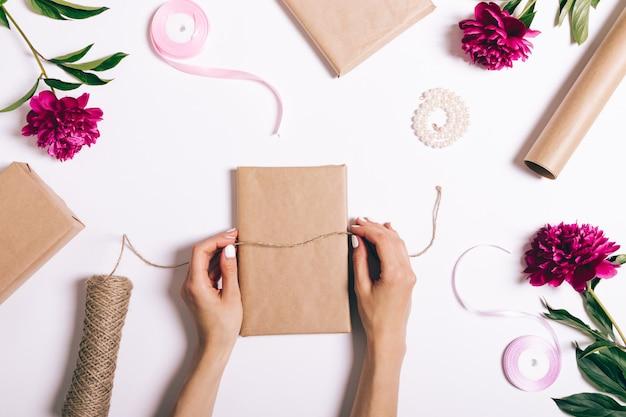 Mani femminili che avvolgono i regali su bianco