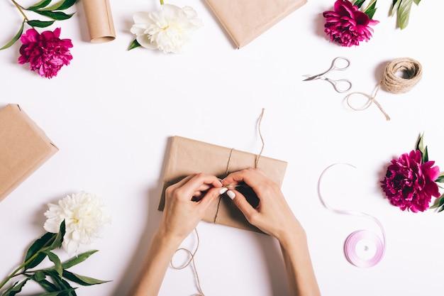 Mani femminili che avvolgono i regali sulla tavola bianca