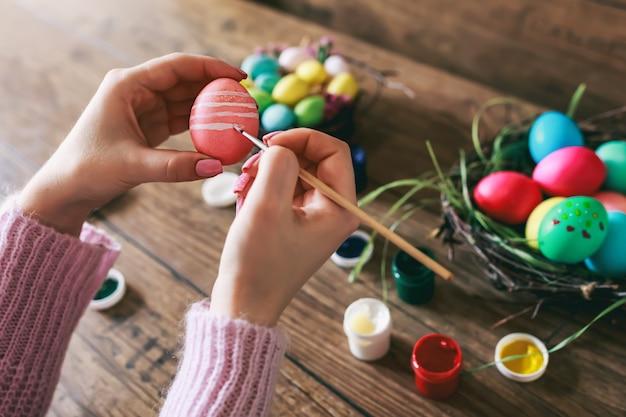 Mani femminili che dipingono le uova di pasqua sulla tavola di legno scura