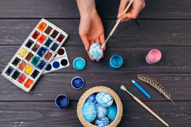 Mani femminili che dipingono le uova di pasqua