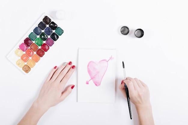 Mani femminili che disegnano con il cuore rosa degli acquerelli