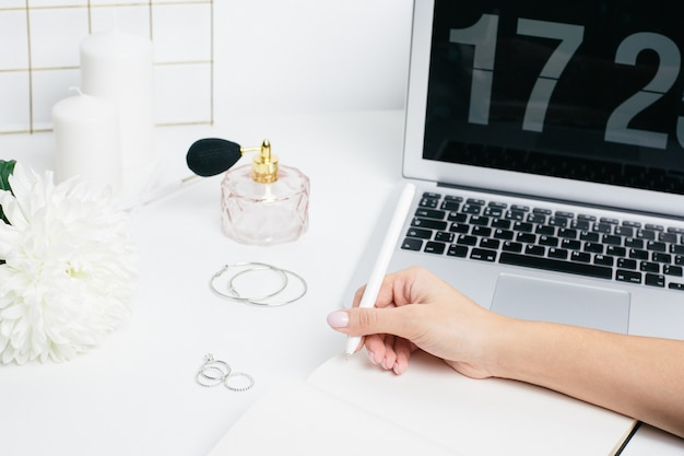 Mani femminili che fanno le note in un blocco note su una tavola bianca con una tastiera del computer portatile